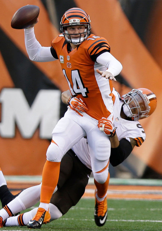 . Cincinnati Bengals quarterback Andy Dalton (14) is pressured by Cleveland Browns outside linebacker Jabaal Sheard in the first half of an NFL football game on Sunday, Nov. 17, 2013, in Cincinnati. (AP Photo/Al Behrman)