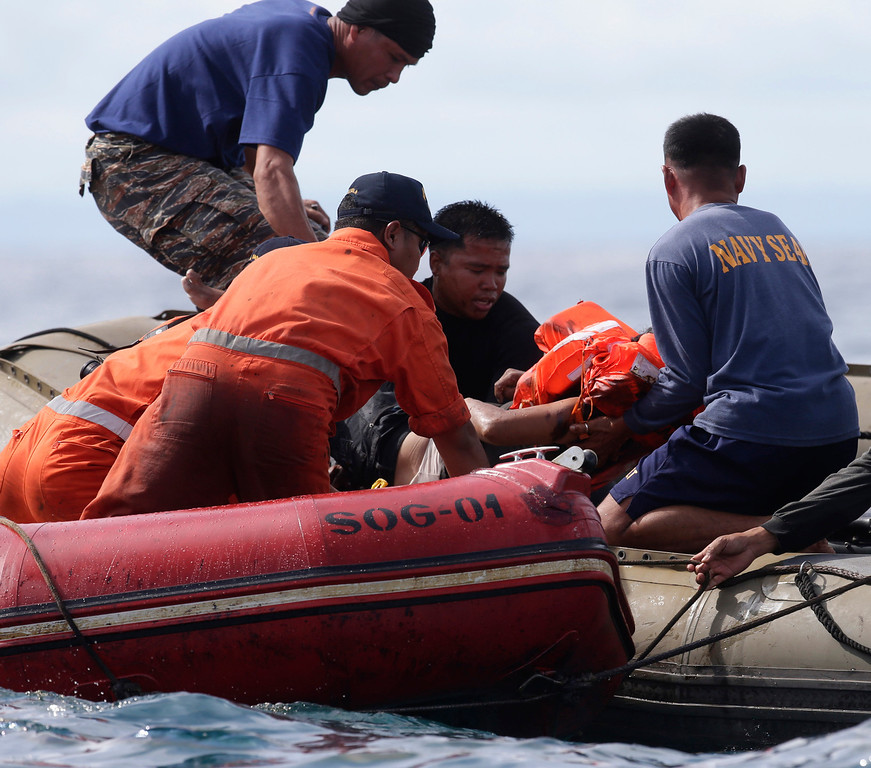 . Philippine Navy and Philippine Coast Guard divers retrieve a body from the waters off the coast of Talisay city, Cebu province, in central Philippines Saturday Aug. 17, 2013, a day after a passenger ferry MV Thomas of Aquinas collided with a cargo ship Sulpicio Express Siete. Divers combed through a sunken ferry Saturday to retrieve the bodies of more than 200 people still missing from an overnight collision with a cargo vessel near the central Philippine port of Cebu that sent passengers jumping into the ocean and leaving many others trapped. At least 28 were confirmed dead and hundreds rescued. The captain of the ferry MV Thomas Aquinas, which was approaching the port late Friday, ordered the ship abandoned when it began listing and then sank just minutes after collision with the MV Sulpicio Express, coast guard deputy chief Rear Adm. Luis Tuason said. (AP Photo/Bullit Marquez)