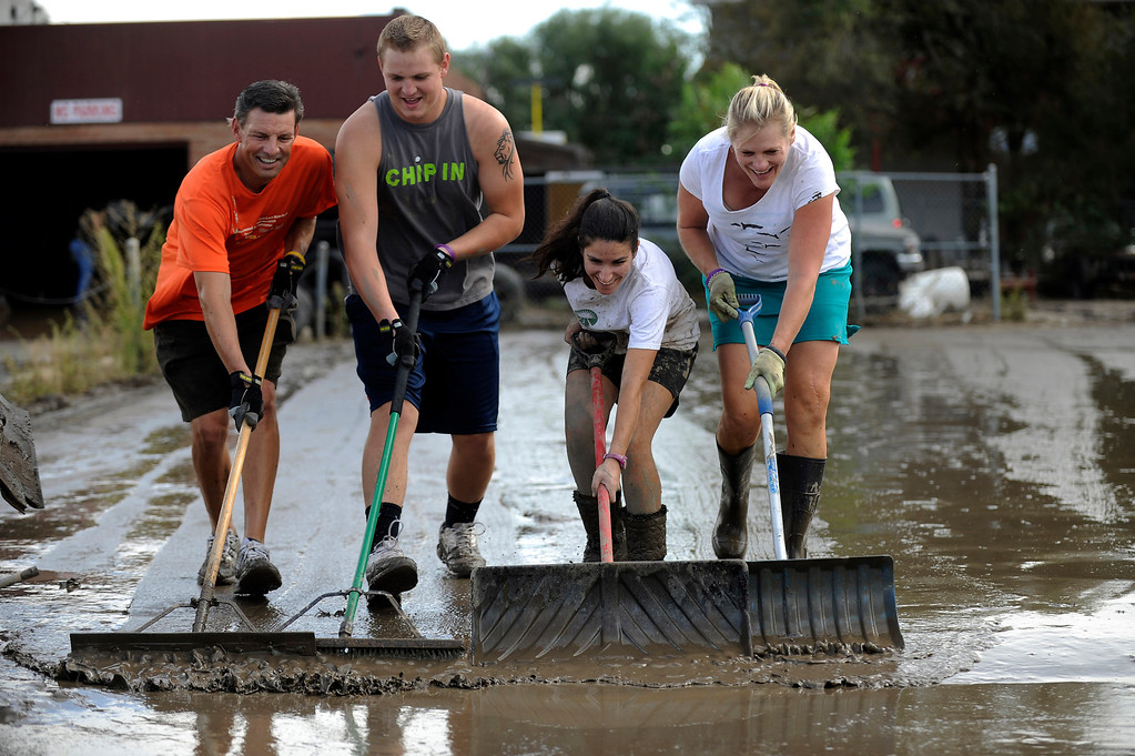 . LONGMONT, CO - SEPTEMBER 14: Rick Phillips, left, Logan Phillips, 18, Sharon Shaw and Suzanne Phillips create a human plow as they push mud and flood waters out of the parking lot of a joint business on Boston Ave in Longmont, Colorado on September 14, 2013. Clean up began on Saturday in downtown Longmont following heavy flooding in previous days. (Photo by Seth McConnell/The Denver Post)