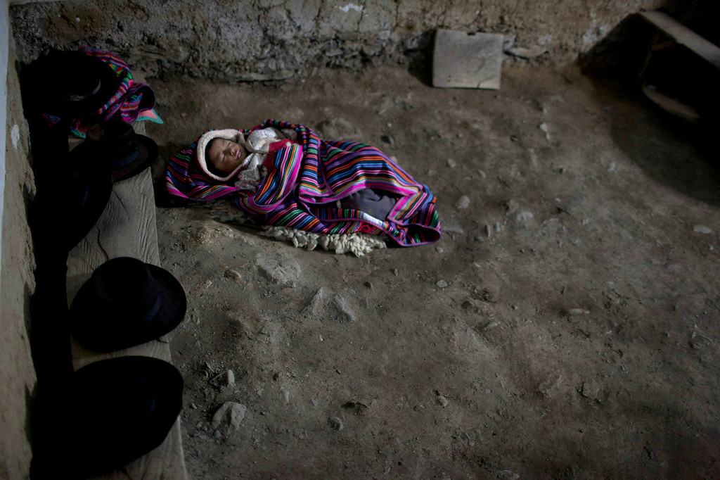 . Junior Edgar, 4, sleeps in the corner of an evangelical church in Chaca, Peru, as his mother participates in the evening service, after attending a mass burial. Peru has failed to address the unhealed wounds of thousands of families, most of them poor, Quechua-speaking peasants, traumatized by the country\'s 1980-2000 conflict. Ten years after a Truth and Reconciliation Commission of respected academics issued a report on the conflict, few of its recommendations have been heeded.   (AP Photo/Rodrigo Abd)