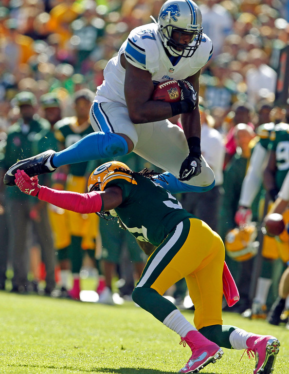 . Detroit Lions\' Brandon Pettigrew tries to leap over Green Bay Packers\' Davon House after a catch during the first half of an NFL football game Sunday, Oct. 6, 2013, in Green Bay, Wis. (AP Photo/Mike Roemer)