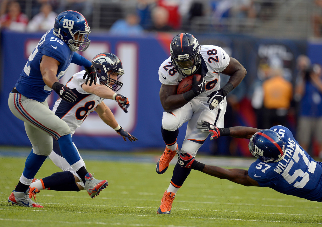 . Broncos running back Montee Ball (28) of the Denver Broncos picks up a big gain after catching a pass and gets tripped up by outside linebacker Jacquian Williams (57) of the New York Giants during the first quarter September 15, 2013 MetLife Stadium. (Photo by John Leyba/The Denver Post)
