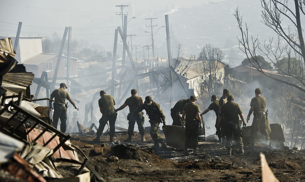 . Soldiers work at an area of Valparaiso, Chile, affected by a huge fire, on April 14, 2014. Emergency responders struggled Monday with outbreaks from a deadly blaze that tore through parts of an historic Chilean port city, as authorities hoped to have control of the flames in two to three days.   AFP PHOTO/MARTIN BERNETTI/AFP/Getty Images