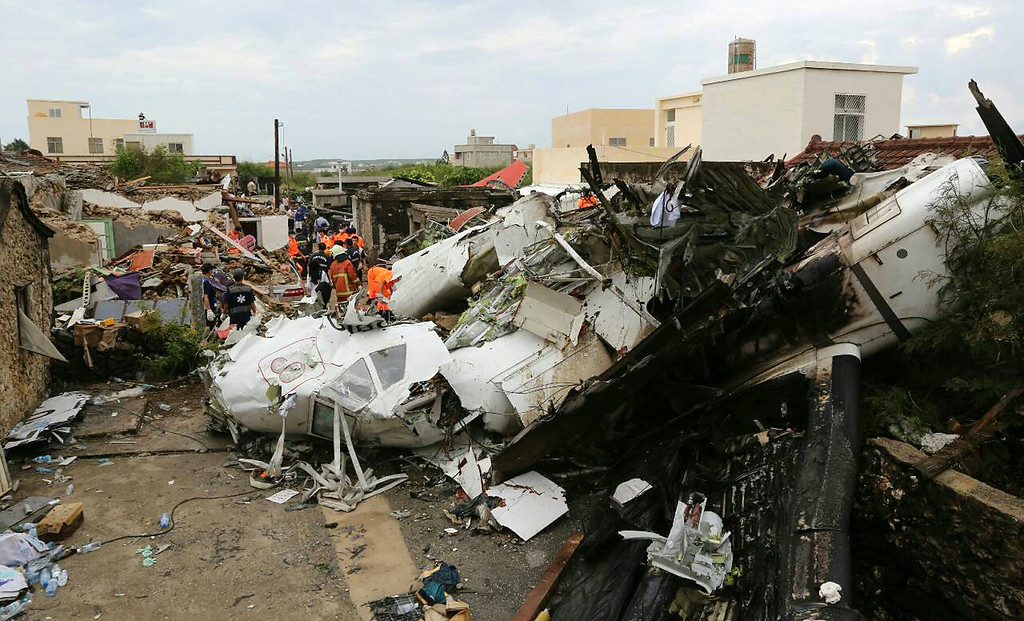 . Rescue workers survey the wreckage of TransAsia Airways Flight GE222 on the Taiwanese island of Penghu Thursday, July 24, 2014. (AP Photo)