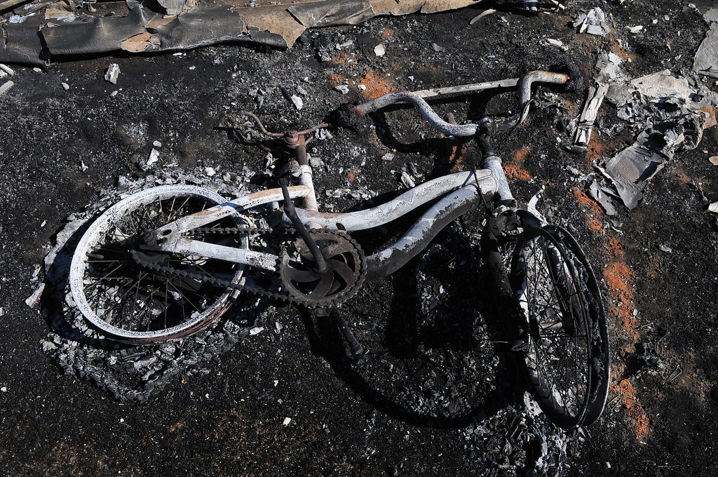 . A charred bicycle sits in the remains of a trailer home the day after a wildfire tore through the area on Monday, May 5, 2014 in Guthrie, Oklahoma. Firefighters worked through the night and into early Monday to battle the large wildfire that destroyed at least six homes and left at least one person dead after a controlled burn spread out of control in central Oklahoma. (AP Photo/Nick Oxford)
