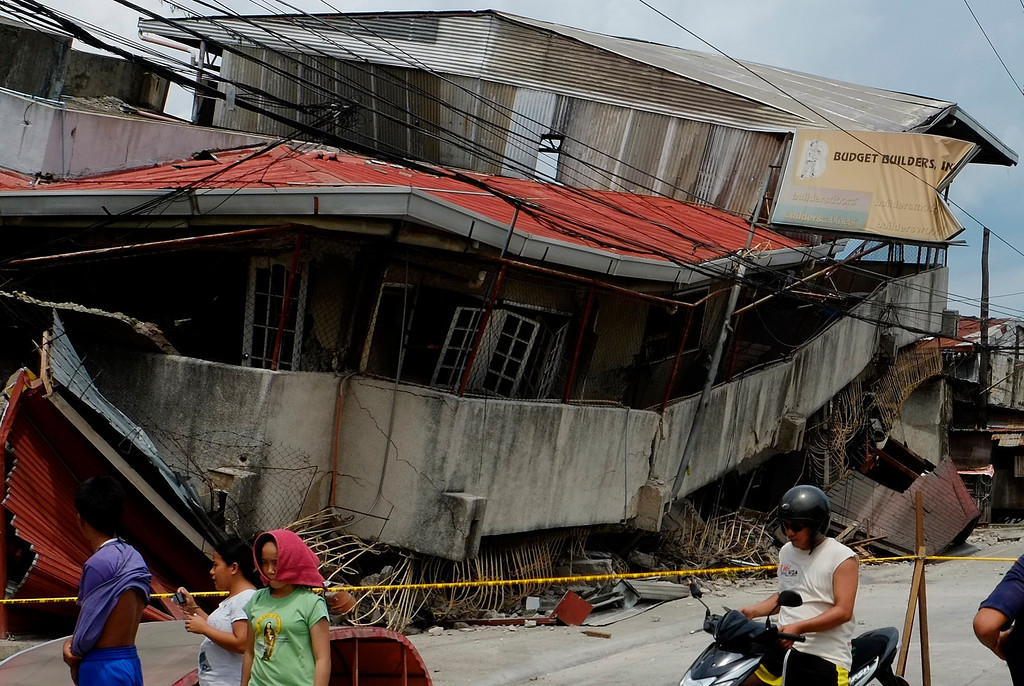 . Residents walk past a damaged structure in Cebu, central Philippines on Tuesday Oct. 15, 2013. A 7.2-magnitude earthquake struck in the central Philippines on Tuesday morning, collapsing roofs and buildings, cracking walls and roads and killing several people. (AP Photo/Erwin Lim)