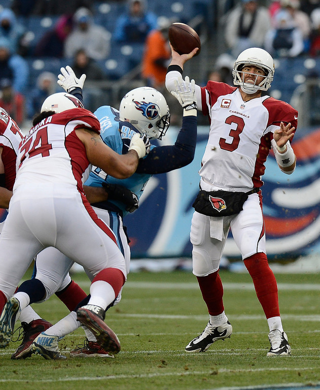 Description of . Arizona Cardinals quarterback Carson Palmer (3) passes as guard Paul Fanaika (74) blocks Tennessee Titans defensive tackle Jurrell Casey (99) in the first quarter of an NFL football game Sunday, Dec. 15, 2013, in Nashville, Tenn. (AP Photo/Mark Zaleski)
