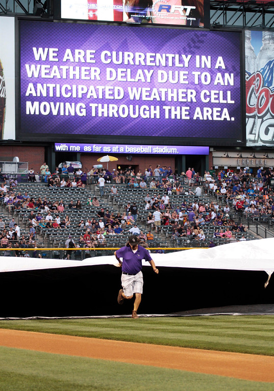 . A grounds crew member helps pull a tarp across the infield as the Colorado Rockies against the PIttsburgh Pirates baseball game is delayed due to lightning storms in Denver, Saturday, Aug. 10, 2013.(AP Photo/Joe Mahoney)