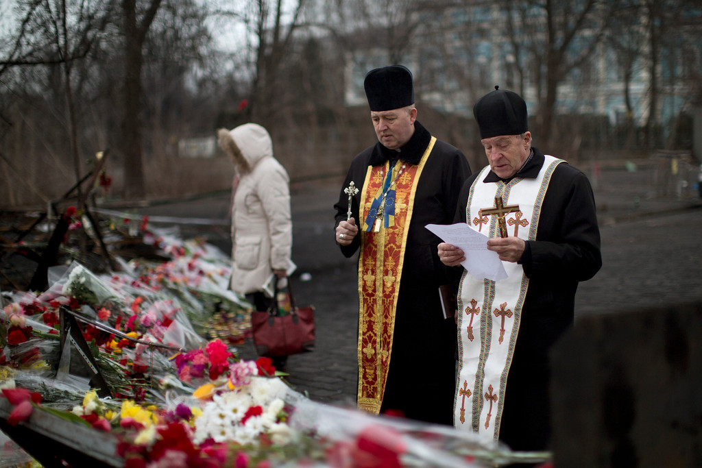 . Two priests pray at a memorial for the people killed in clashes with the police at Kiev\'s Independence Square, the epicenter of the country\'s current unrest, Ukraine, Friday, Feb. 28, 2014. Russian military were blocking the airport in the Black Sea port of Sevastopol in Crimea near the Russian naval base while unidentified men were patrolling another airport serving the regional capital, Ukraine\'s new Interior Minister Arsen Avakov said on Friday. (AP Photo/Emilio Morenatti)