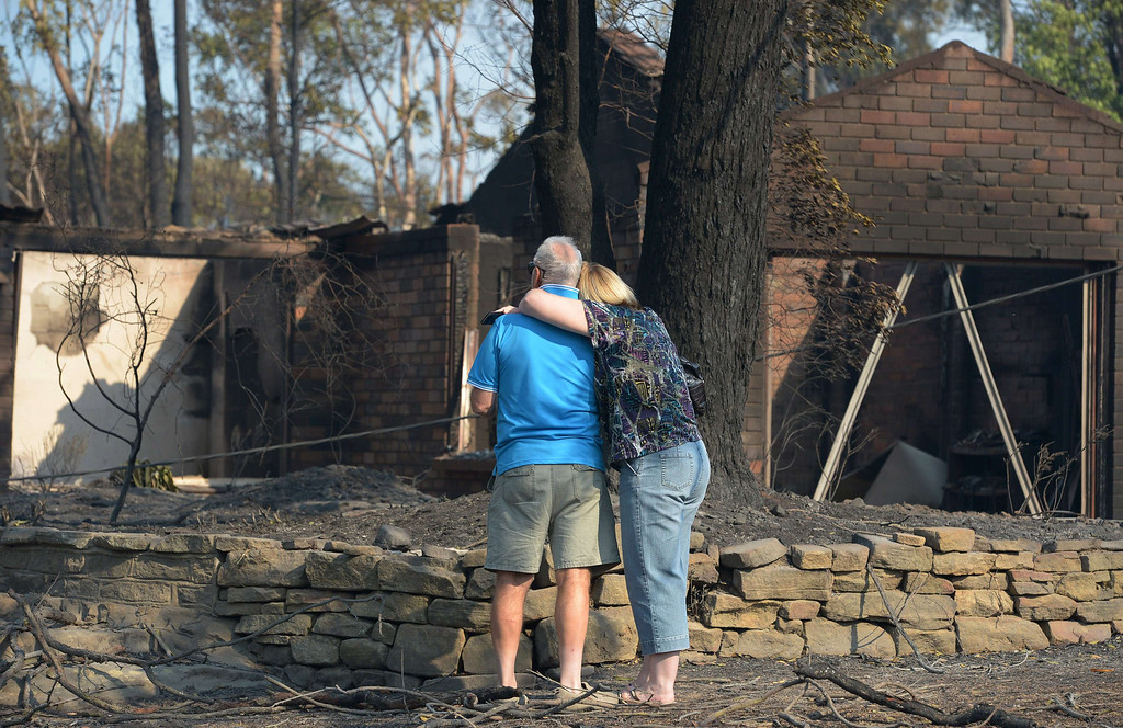 . A couple look at a house burnt out by bush fires in Winmalee in Sydney\'s Blue Mountains on October 18, 2013.  TOPSHOTS   AFP PHOTO / Greg WOOD/AFP/Getty Images
