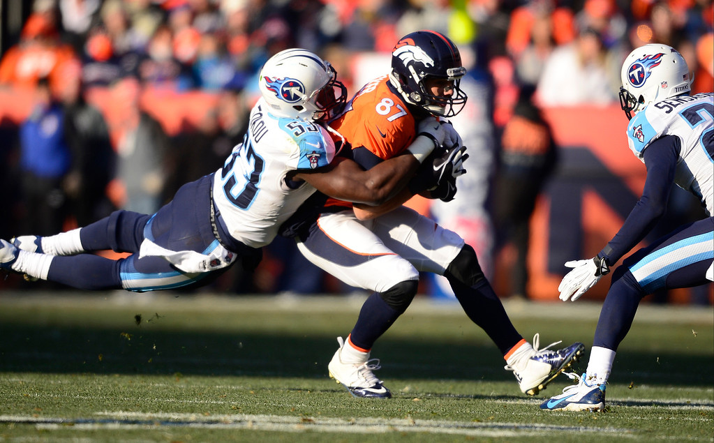 . Denver Broncos wide receiver Eric Decker (87) catches a pass and is tackled by Tennessee Titans middle linebacker Moise Fokou (53). (Photo by AAron Ontiveroz/The Denver Post)