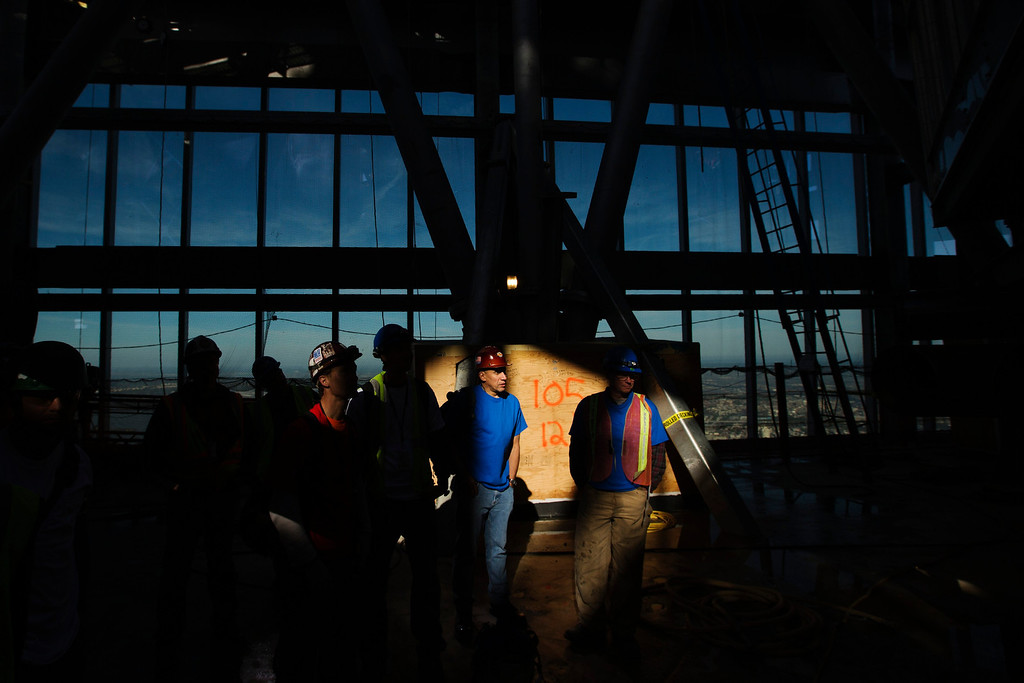 . Workers stand in a shaft of sunlight on the 105th floor of the One World Trade Center after the final piece of the building\'s spire was attached in New York May 10, 2013. Workers cheered and whistled as they completed the spire on New York\'s One World Trade Center on Friday, raising the building to its full height of 1,776 feet and helping fill a void in the skyline left by the September 11, 2001 attacks. REUTERS/Lucas Jackson