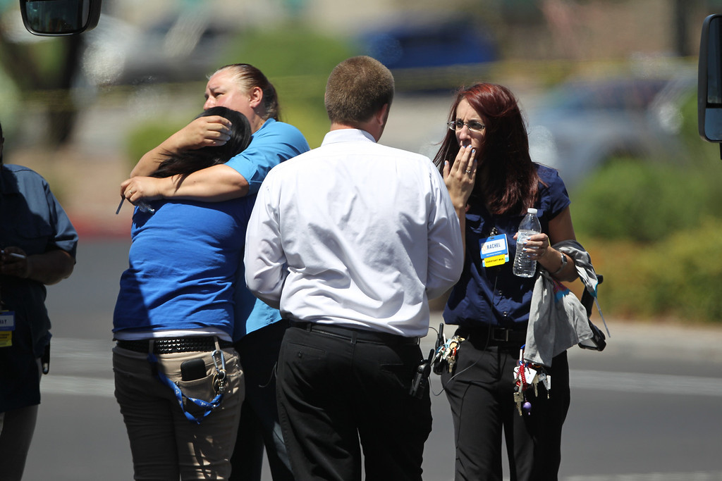 . Wal-Mart employees hug outside a store after a shooting at the store and a nearby CiCiís Pizza in Las Vegas, Sunday, June 8, 2014. A man and a woman ambushed two police officers eating lunch at the Las Vegas restaurant, fatally shooting them at point-blank range before fleeing to a nearby Wal-Mart where they killed a third person and then themselves in an apparent suicide pact, authorities said Sunday. (AP Photo/Las Vegas Review-Journal, K.M. Cannon)