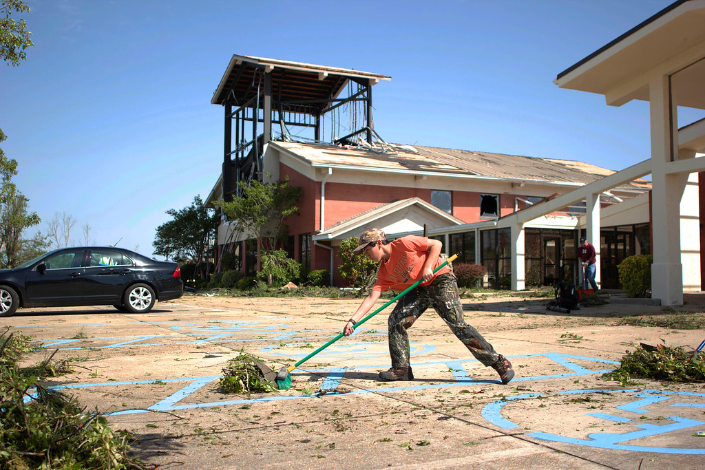 . Zach Barrington brushes away debris at Saint Luke United Methodist church on Tuesday, April 29, 2014 in Tupelo, Miss.  (AP Photo/Hunt Mercier)