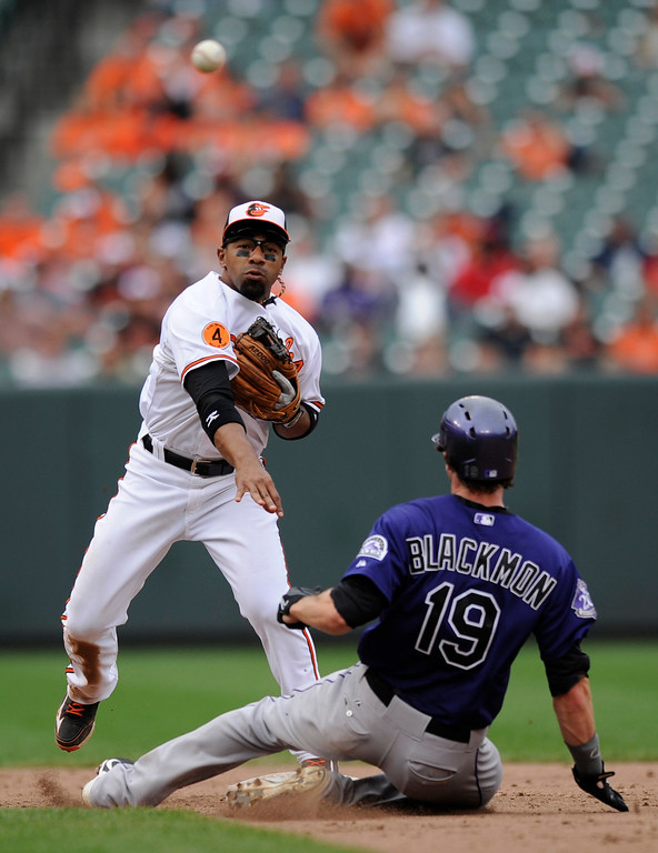 . Colorado Rockies\' Charlie Blackmon (19) is out at second as Baltimore Orioles second baseman Alexi Casilla, left, throws to first to complete a double-play on a ground ball by Charlie Culberson during the ninth inning of a baseball game on Sunday, Aug. 18, 2013, in Baltimore. The Orioles won 7-2. (AP Photo/Nick Wass)
