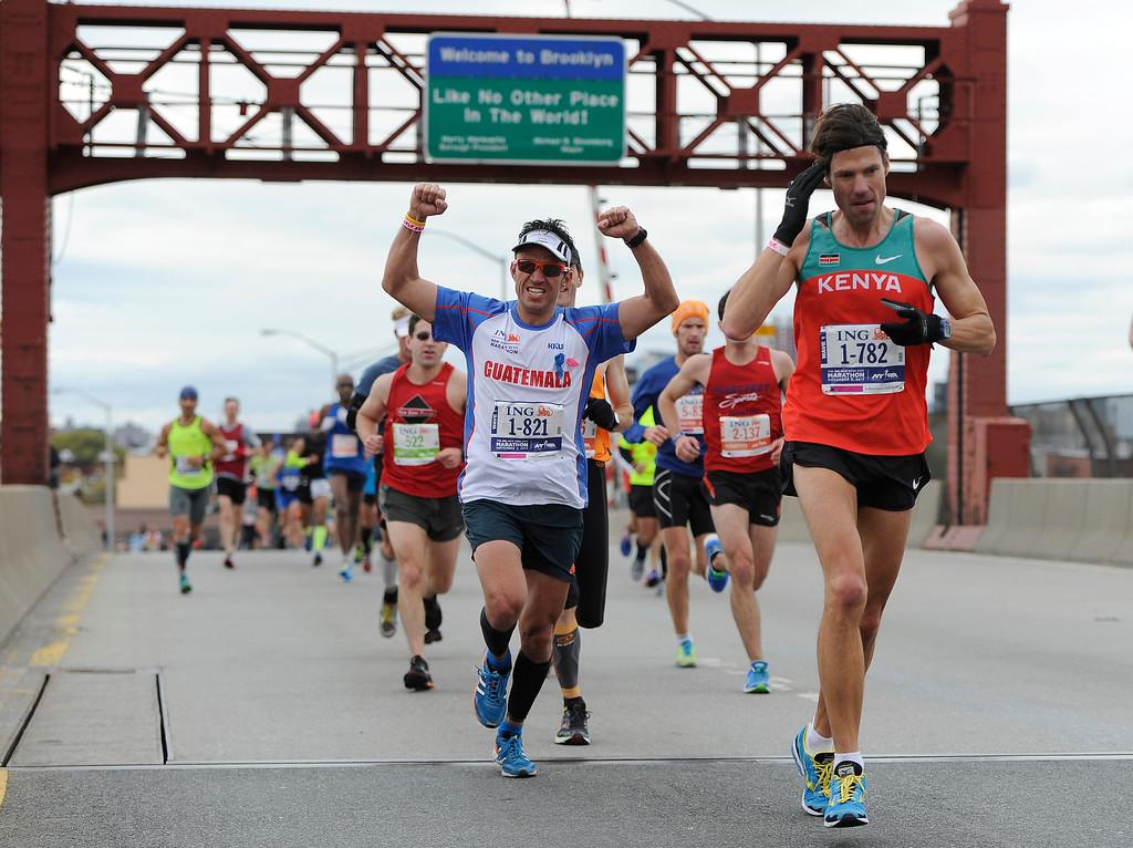 . A runner celebrates as he crosses the Pulaski Bridge into the Queens borough of New York during the New York City Marathon on Sunday, Nov. 3, 2013. New York. (AP Photo/Kathy Kmonicek)