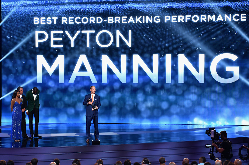 . NFL player Peyton Manning of the Denver Broncos (R) accepts the Best Record-Breaking Performance award from former NFL player Dan Marino (L) and NBA player Kevin Durant (C) onstage during the 2014 ESPYS at Nokia Theatre L.A. Live on July 16, 2014 in Los Angeles, California.  (Photo by Kevin Winter/Getty Images)