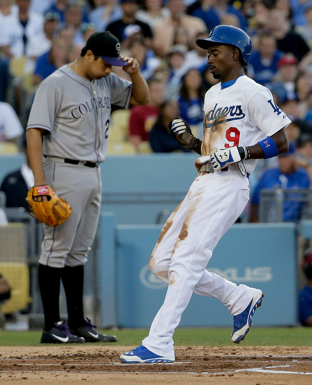 . Los Angeles Dodgers\' Dee Gordon, right, scores on a sacrifice fly by teammate Yasiel Puig as Colorado Rockies starting pitcher Jorge De La Rosa looks down during first inning of a baseball game in Los Angeles, Wednesday, June 18, 2014. (AP Photo/Chris Carlson)
