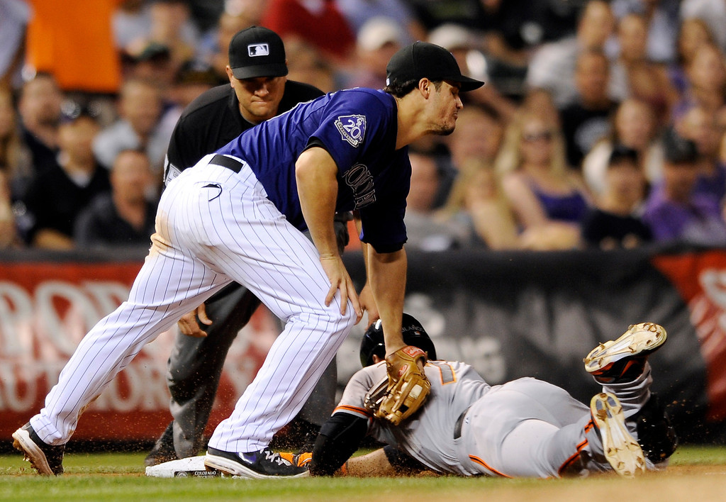 . Colorado Rockies third baseman Nolan Arenado (28) is late with the tag on San Francisco Giants\' Gregor Blanco (7) at third during the seventh inning of a baseball game on Tuesday, Aug. 27, 2013, in Denver. Blanco hit a triple on the play.  (AP Photo/Jack Dempsey)