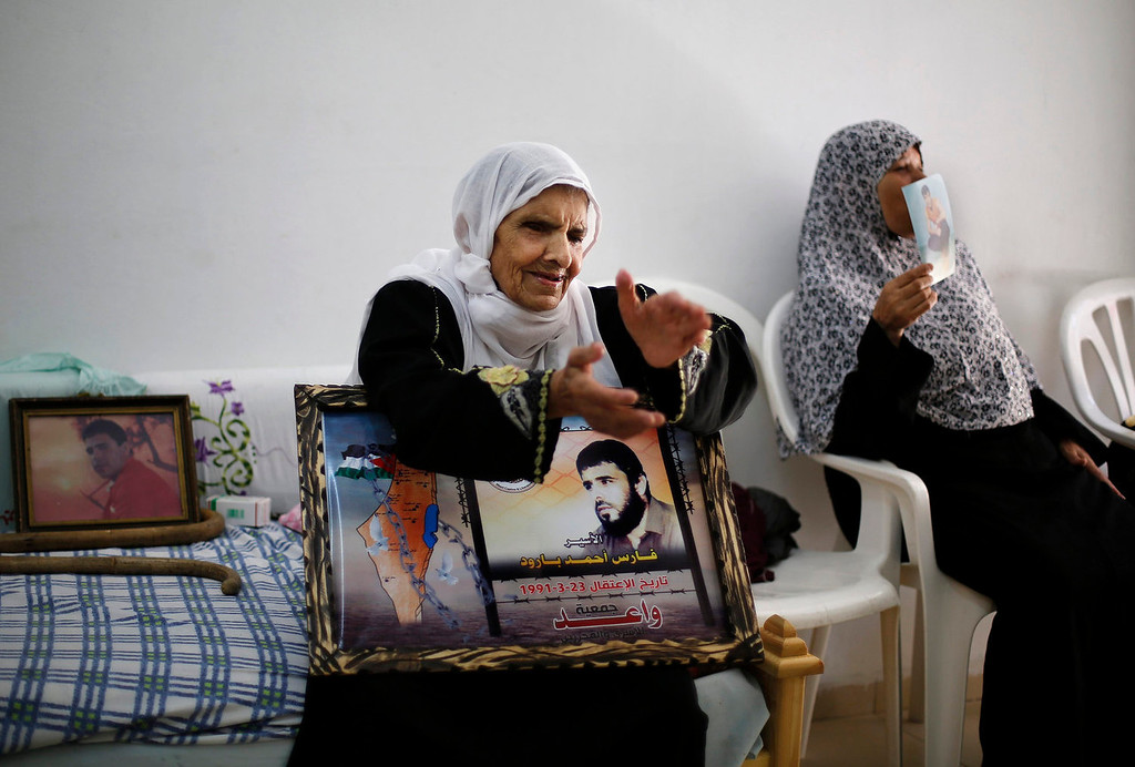. Rayya (L), mother of Palestinian Fares Baroud (picture), who has been held prisoner by Israel for 22 years, celebrates after hearing news on the possible release of her son in her house at Shati refugee camp in Gaza City July 28, 2013. Baroud was expected to be among more than 100 Arab prisoners to be released as a step to renew stalled peace talks with the Palestinians ahead of plans to convene negotiators in Washington later this week.  Israeli ministers have yet to vote on the releases.   REUTERS/Suhaib Salem
