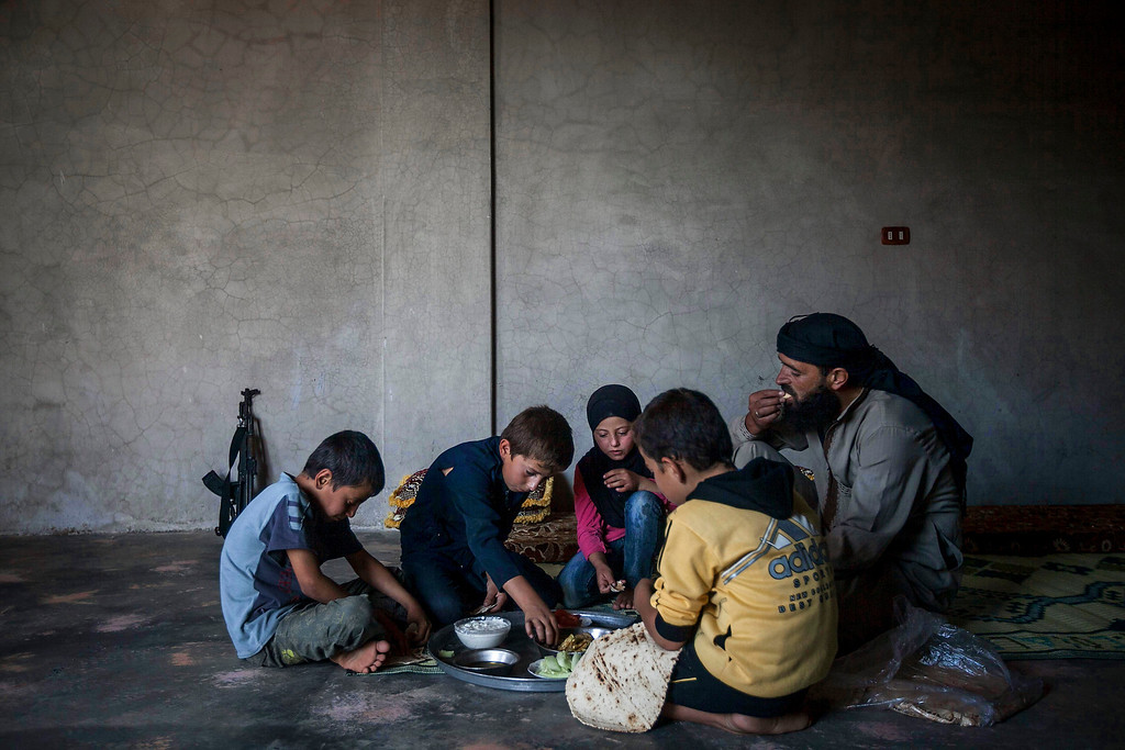 . In this Sunday, Sept. 29, 2013 photo, Ahmed al-Fikri sits with his sons and daughter, among them 12-year-old Abdo al-Fikri, second left, to eat lunch at their family house in Madaya village after school in the Idlib province countryside of Syria. It has been a year since al-Fikri and his siblings were last in school. The area has seen ongoing battles between opposition forces and troops loyal to President Bashar Assad, and like pretty much everything else in Madaya, the school was forced to shut down because of the violence. (AP Photo)
