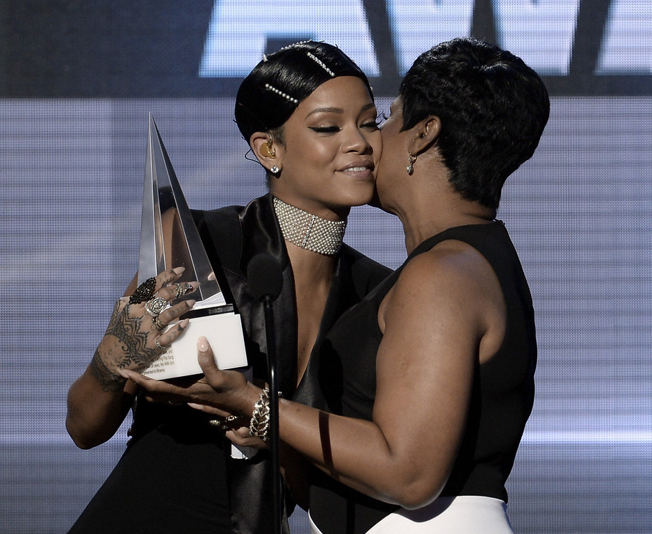 . Singer Rihanna (L) accepts the AMA Icon Award from mother Monica Braithwaite Fenty onstage during the 2013 American Music Awards at Nokia Theatre L.A. Live on November 24, 2013 in Los Angeles, California.  (Photo by Kevin Winter/Getty Images)