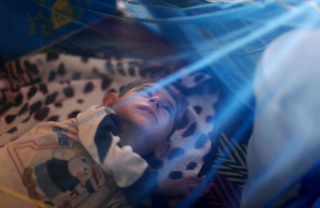 . FILE - A Syrian boy, who fled his home with his family due to fighting between the Syrian government troops and the rebels, lies on the ground under a mosquito net as he and his family take refuge at the Bab Al-Salameh border crossing, in hopes of entering one of the refugee camps in Turkey, near the Syrian town of Azaz, Tuesday, Aug. 28, 2012. (AP Photo/Muhammed Muheisen, File)