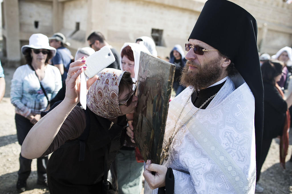 . QASR AL YAHUD, WEST BANK - JANUARY 18:  An Orthodox Christian kisses a holy image held by an Orthodox monk during an Epiphany celebrations near the Jordan River January 18, 2014 at the Qasir al-Yahud baptismal site near Jericho, in the West Bank. Pilgrims gathered for the annual celebration at the site that the Eastern churches believes Jesus was baptised by John.  (Photo by Ilia Yefimovich/Getty Images)