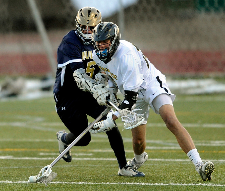 . LITTLETON, CO. - APRIL 10: Mustangs\' senior attack Austin Smith (5) challenged Warriors senior defenseman Drew Danuser (10) for a loose ball in the first half. The Mullen High School boy\'s lacrosse team defeated Arapahoe 8-7 Wednesday night, April 10, 2013. Photo By Karl Gehring/The Denver Post)
