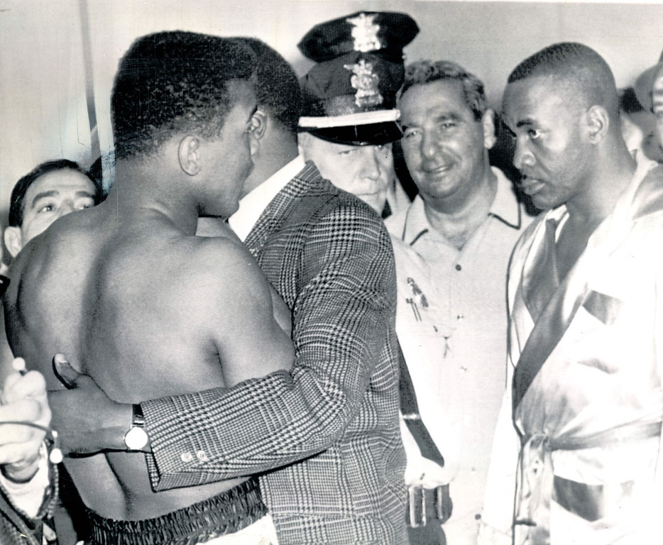 . Cassius Clay (left) was his usual brash self at Tuesday\'s weigh-in for his fight with heavyweight champion Sonny Liston Tuesday night at Miami Beach.  But even the fact Clay was slapped a $2,500 fine for his antics couldn\'t force a smile on glowering Liston (right).  The champ weighed in at 218, while challenger Clay scaled 210 1/2.   MIAMI BEACH, Fla.,  1964 AP Wirephoto