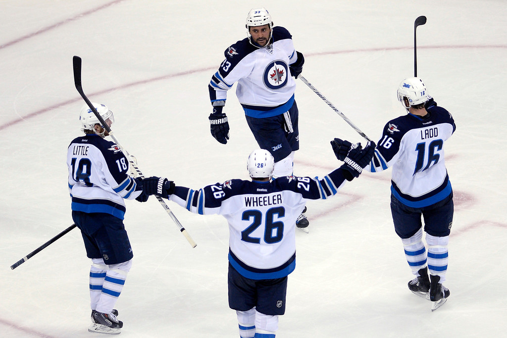 . Dustin Byfuglien (33) of the Winnipeg Jets celebrates his goal with teammates Bryan Little (18), Blake Wheeler (26) and Andrew Ladd (16) against the Colorado Avalanche during the first period. (Photo by AAron Ontiveroz/The Denver Post)