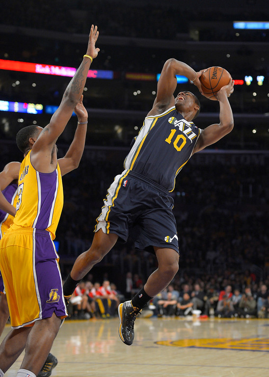 . Utah Jazz guard Alec Burks, right, puts up a shot as Los Angeles Lakers forward Shawne Williams defends during the first half of an NBA basketball game, Friday, Jan. 3, 2014, in Los Angeles. (AP Photo/Mark J. Terrill)