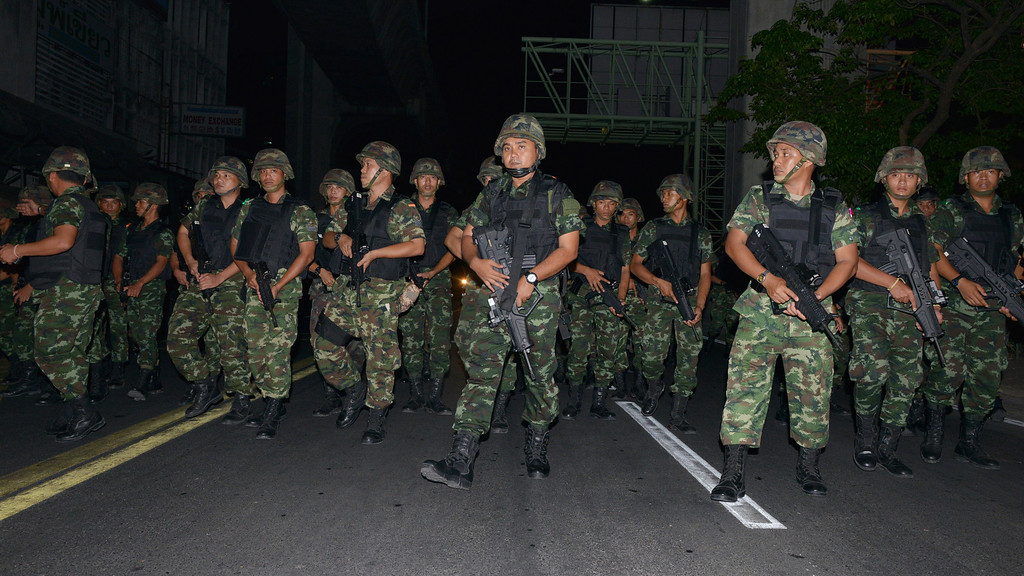 . Thai army soldiers advance through the city centre after protesters hold an anti-coup rally on May 23, 2014 in Bangkok, Thailand. Anti-coup protesters rallied in Bangkok\'s shopping district, a day after the military seized control in a bloodless coup. Martial law imposes a 10pm to 5am curfew and public assembly is banned. (Photo by Rufus Cox/Getty Images)