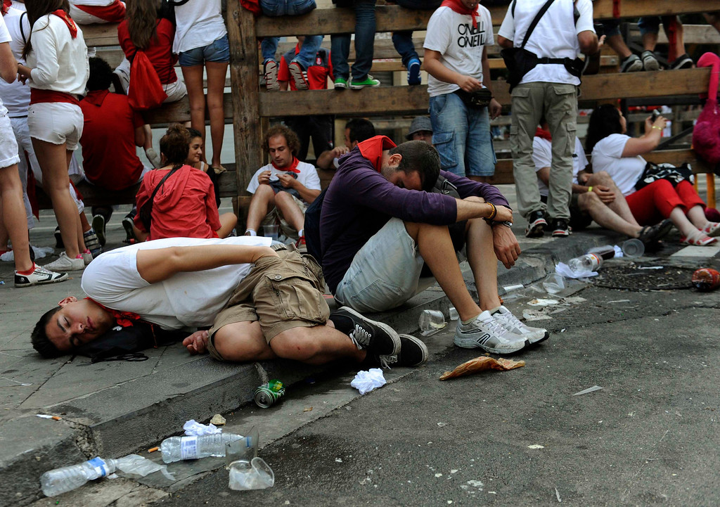 . Revellers sleep at the Telefonica corner before the fourth running of the bulls of the San Fermin festival in Pamplona July 10, 2013. Several runners suffered light injuries in a run that lasted two minutes and fourteen seconds, according to local media.  REUTERS/Eloy Alonso