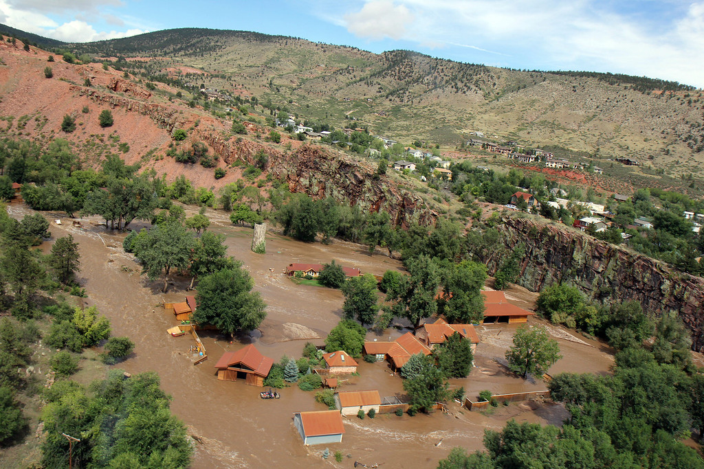 . Homes in Lyons, Colo. are surrounded by water as flooding continues to devastate the Front Range as thousands are forced to evacuate with an unconfirmed number of structures destroyed Friday, Sept. 13, 2013.  (AP Photo/Colorado Heli-Ops, Dennis Pierce)