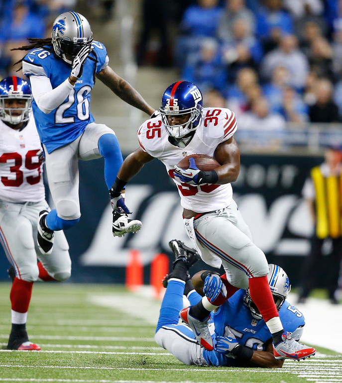. New York Giants running back Andre Brown (35) is chased by Detroit Lions linebacker Rocky McIntosh, bottom, and free safety Louis Delmas (26) during the first quarter of an NFL football game, Sunday, Dec. 22, 2013, in Detroit. (AP Photo/Rick Osentoski)