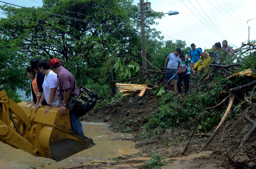 . People are aided with the help of a bulldozer to cross a road after a landslide caused by heavy rains brought by Tropical Storm Manuel on the outskirts of Acapulco, Mexico, Monday Sept. 16, 2013.  Tropical Storm Ingrid and remnants of Tropical Storm Manuel drenched Mexico\'s Gulf and Pacific coasts, flooding towns and cities in a national emergency that federal authorities say has caused at least 34 deaths. (AP Photo/Bernandino Hernandez)