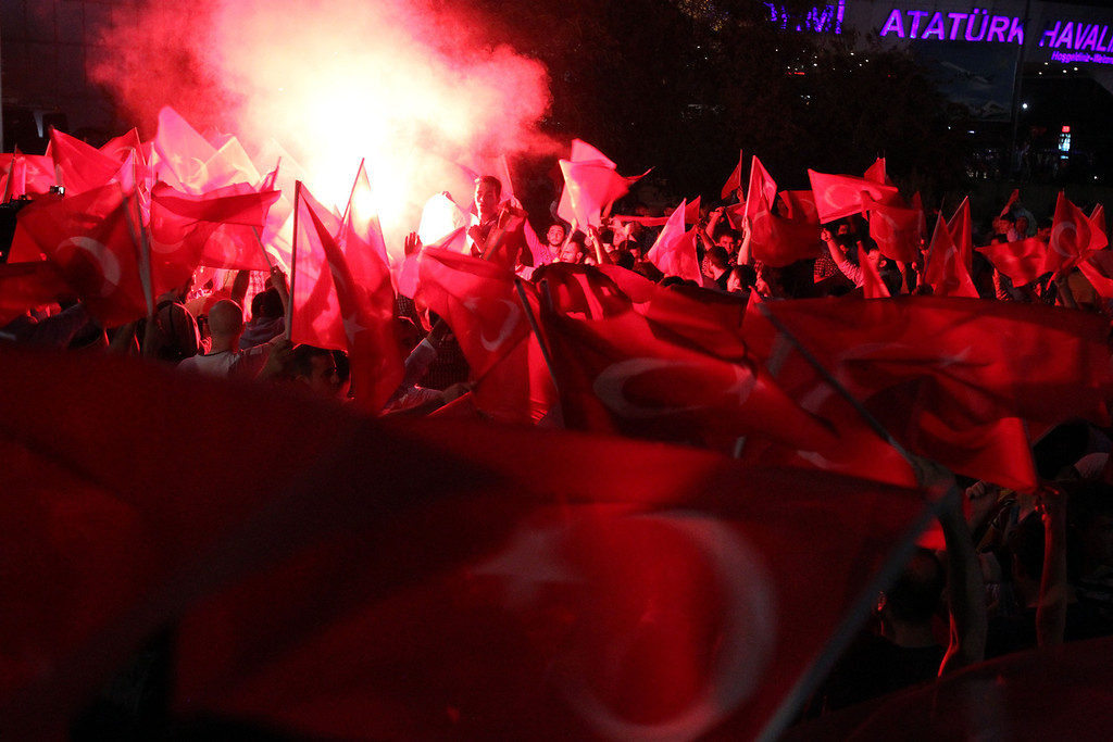 . Supporters of Turkish Prime Minister Recep Tayyip Erdogan light flares upon his arrival at the Ataturk Airport of Istanbul early Friday, June 7, 2013. Erdogan took a combative stance on his closely watched return to the country early Friday, telling supporters who thronged to greet him that the protests that have swept the country must come to an end. In the first extensive public show of support since anti-government protests erupted last week, more than 10,000 supporters cheered Erdogan with rapturous applause outside Istanbul\'s international airport. (AP Photo/Thanassis Stavrakis)