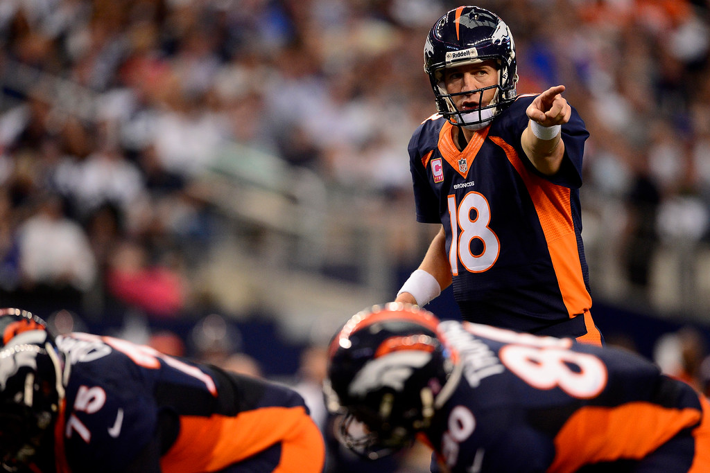 . Peyton Manning (18) of the Denver Broncos makes pre-play adjustments against the Dallas Cowboys during the first half of action at AT&T Stadium. (Photo by AAron Ontiveroz/The Denver Post)