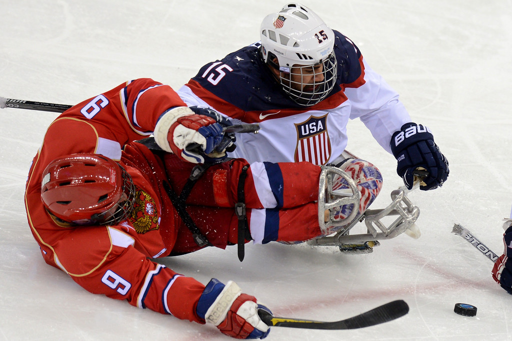 . United States\' Nikko Landeros (R) vies with Russia\'s Konstantin Shikov during Sledge Hockey Final match between Russia and USA at XI Paralympic Olympic games in the Shayba stadium close near Sochi on March 15, 2014. AFP PHOTO/KIRILL  KUDRYAVTSEV/AFP/Getty Images