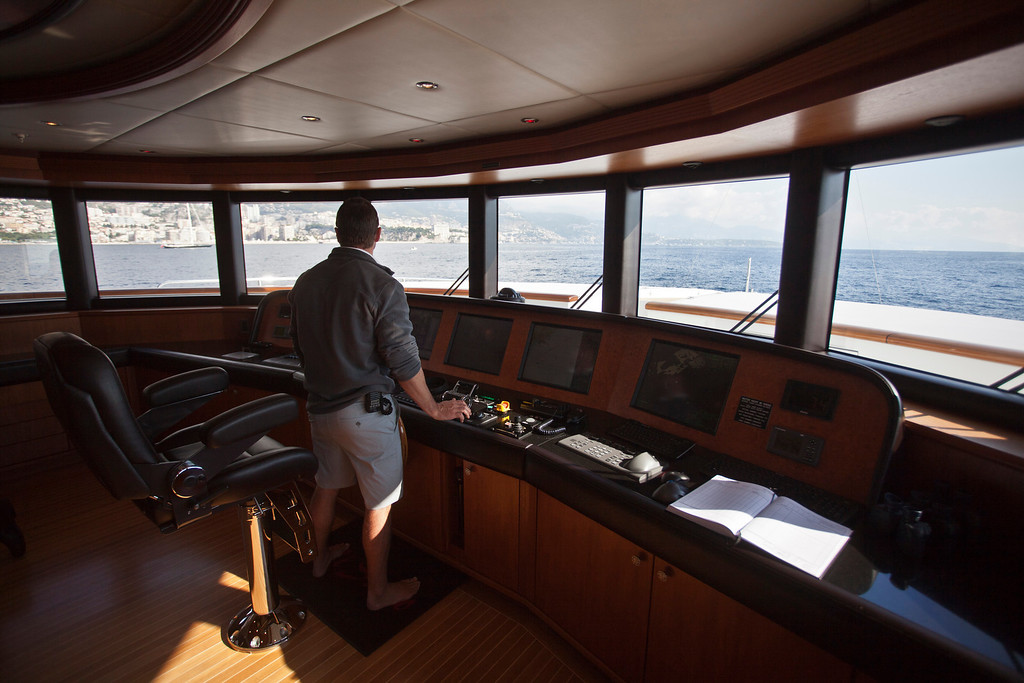 . A crew member stands by controls on the bridge of the 190ft (57.9m) motor yacht Mi Sueno, manufactured by Trinity Yachts LLC, as it sails from the harbor in Nice, France, on Wednesday, Sept. 25, 2013.  Photographer: Balint Porneczi/Bloomberg