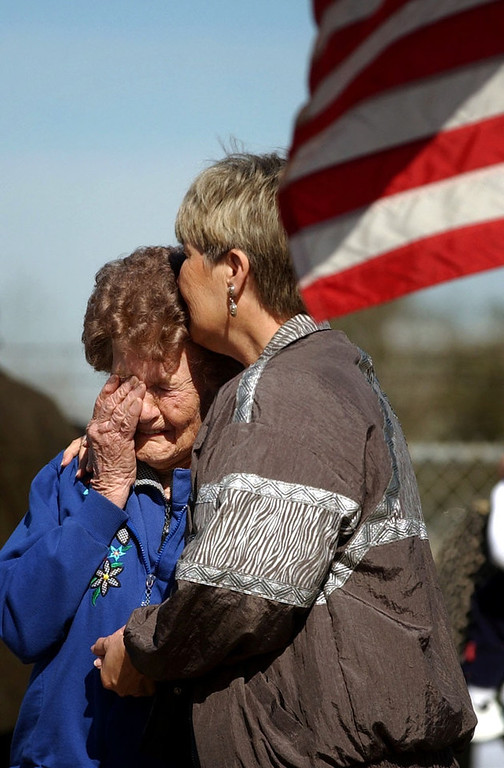 ". Barbara Mikulik  of Houston (right)  kisses her 91-year-old mother Hilda Mikulik of San Angelo, Texas before  the memorial service for space shuttle Columbia astronauts going on with President Bush inside the center on Tuesday, February 4, 2003.  They were outside the gates to the center where flowers, notes, flags are being placed in at a memorial for the astronauts. Barbara brought her mother to the site to witness history and pay a tribute to the ""courageous men and women who did something for us all.\"" CYRUS MCCRIMMON, The Denver Post"