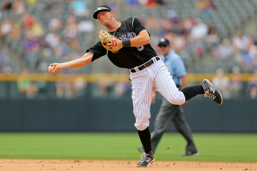 . DENVER, CO - JULY 9:  Second baseman DJ LeMahieu #9 of the Colorado Rockies throws to first base for the first out of the sixth inning against the San Diego Padres at Coors Field on July 9, 2014 in Denver, Colorado. (Photo by Justin Edmonds/Getty Images)