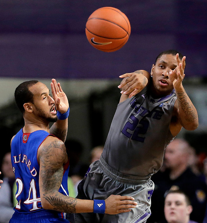 . Kansas State guard Rodney McGruder (22) passes around Kansas guard Travis Releford during the first half of an NCAA college basketball game Tuesday, Jan. 22, 2013, in Manhattan, Kan. (AP Photo/Charlie Riedel)