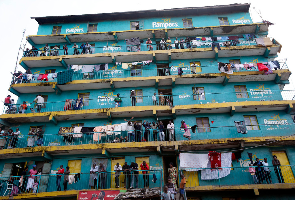 . Supporters of Kenyan Prime Minister Raila Odinga look out from the balconies of a building in the Mathare slum in the Kenyan capital of Nairobi March 9, 2013. REUTERS/Goran Tomasevic