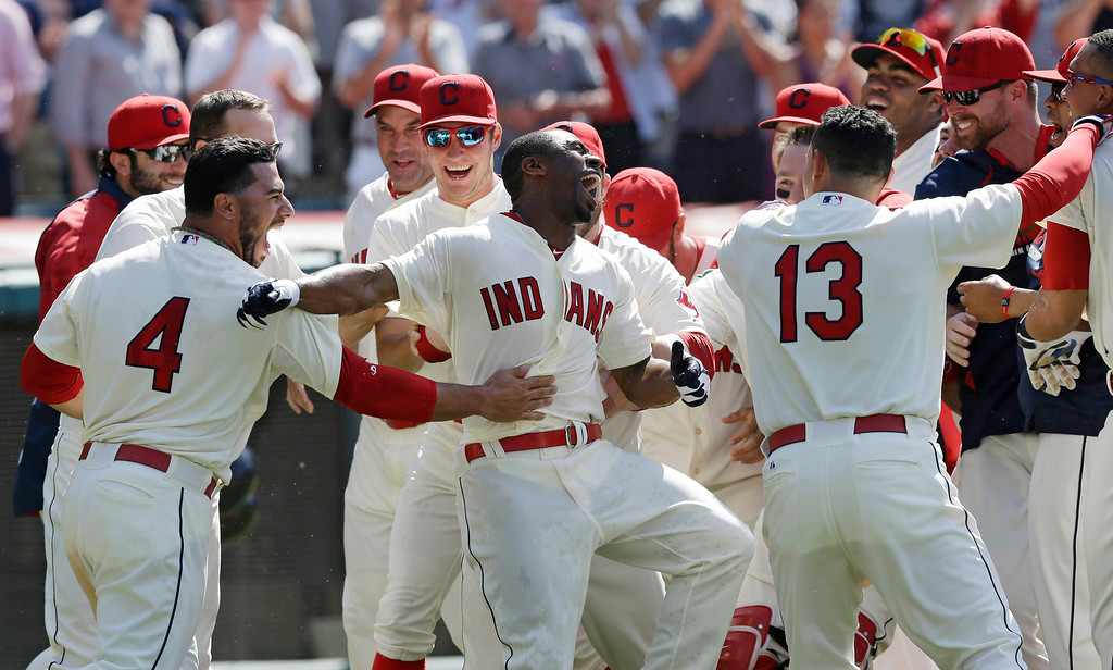 . Cleveland Indians\' Michael Bourn, center, celebrates with teammates after hitting a two-run home run off Colorado Rockies relief pitcher Adam Ottavino in the ninth inning of a baseball game on Sunday, June 1, 2014, in Cleveland. Indians\' Mike Aviles also scored. The Indians defeated the Rockies 6-4. (AP Photo/Tony Dejak)