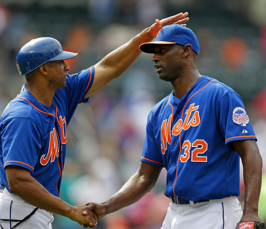 . New York Mets first base coach Tom Goodwin (26) congratulates relief pitcher LaTroy Hawkins (32) after Hawkins pitched a scoreless ninth in the Mets 2-1 victory over the Colorado Rockies in a baseball game in New York, Thursday, Aug. 8, 2013. (AP Photo/Kathy Willens)