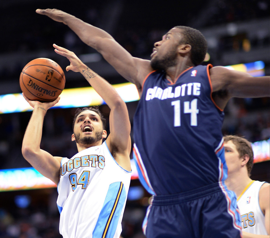 . Evan Fournier of the Denver Nuggets (94) scores against Michael Kidd-Gilchrist of the Charlotte Bobcats (14) in the first half. (Photo by Hyoung Chang/The Denver Post)