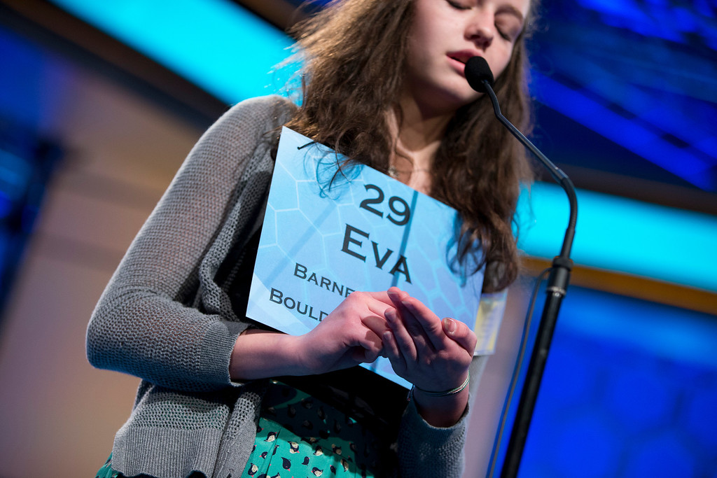 """. Eva Kitlen, 14, of Niwot, Colo., writes out the word \""""kleptocrat\"""" in her hand before spelling it correctly during the semifinal round of the National Spelling Bee, Thursday, May 30, 2013, in Oxon Hill, Md. (AP Photo/Evan Vucci)"""
