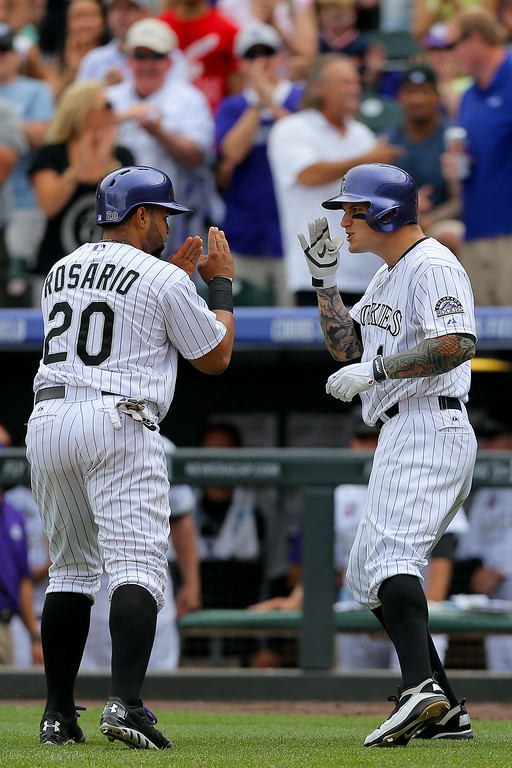 . Brandon Barnes #1 of the Colorado Rockies celebrates his two run home run with Wilin Rosario #20 during the fourth inning against the Pittsburgh Pirates at Coors Field on July 27, 2014 in Denver, Colorado. The Pirates defeated the Rockies 7-5. (Photo by Justin Edmonds/Getty Images)
